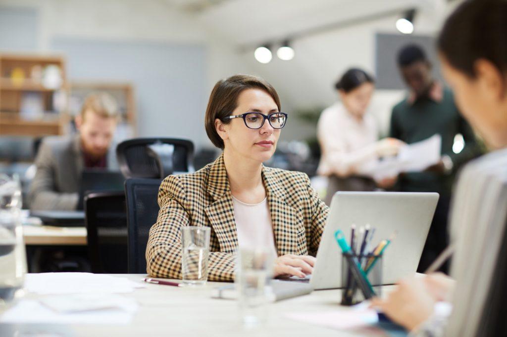 businesswoman using a laptop in an open office environment
